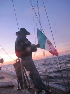 Raising the courtesy flag at sunset